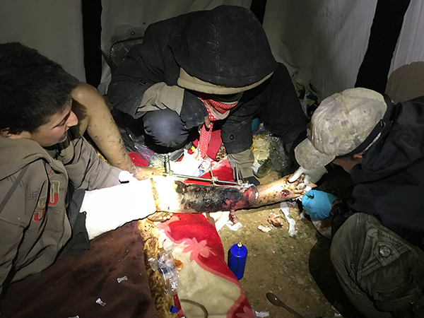Joseph, a Karen medic, helps treat a boy wounded by the Syrian Army.
