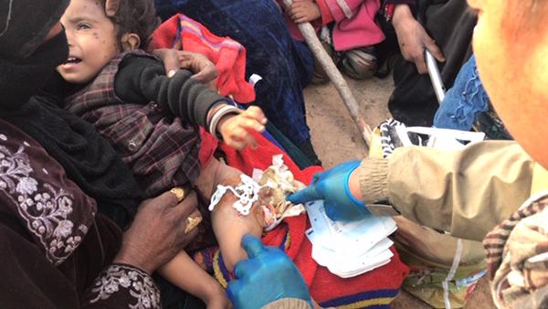 Eliya, a Karen medic, treats a child shot by ISIS