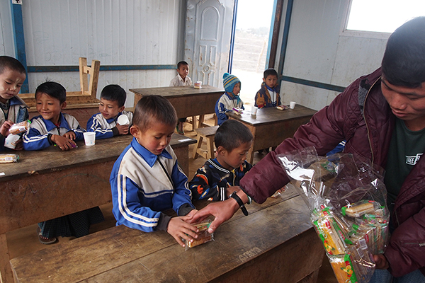A Ranger gives out snacks to IDP children.