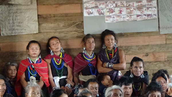 Karenni women stand at the back of a packed room during a GLC program.