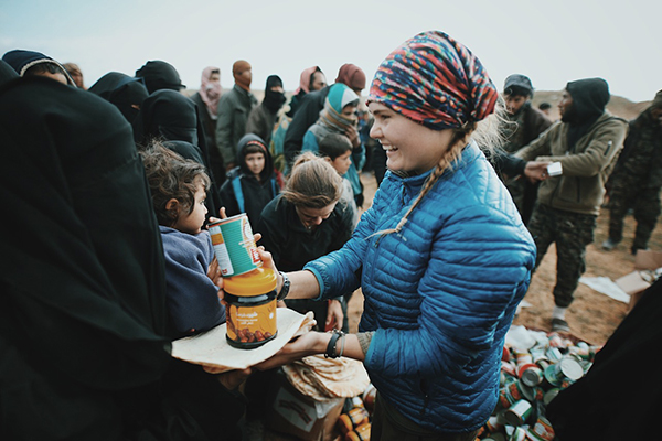 Sahale gives food to an ISIS wife and child after they fled Baghouz.