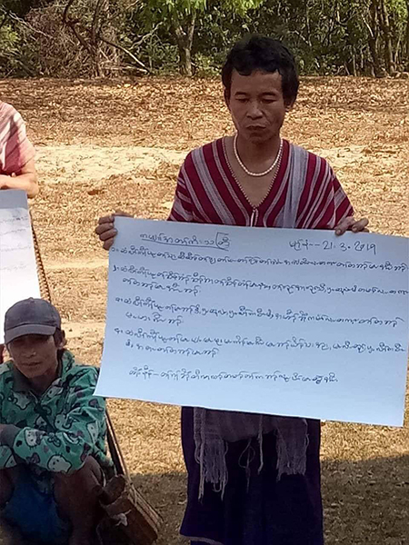 A villager holds up a sign protesting the Burma Army building a road and bridge in Karen State.