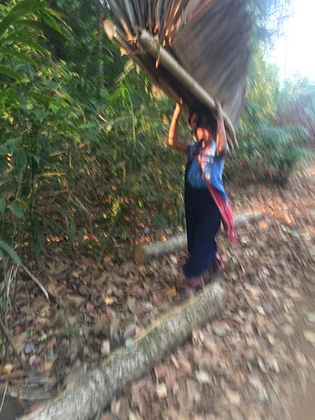 A villager from Pa Kaw Hta Village carries away part of a house into the jungle.