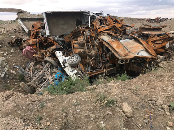 Vehicles in Baghouz that once sheltered ISIS, now in a rubble pile.
