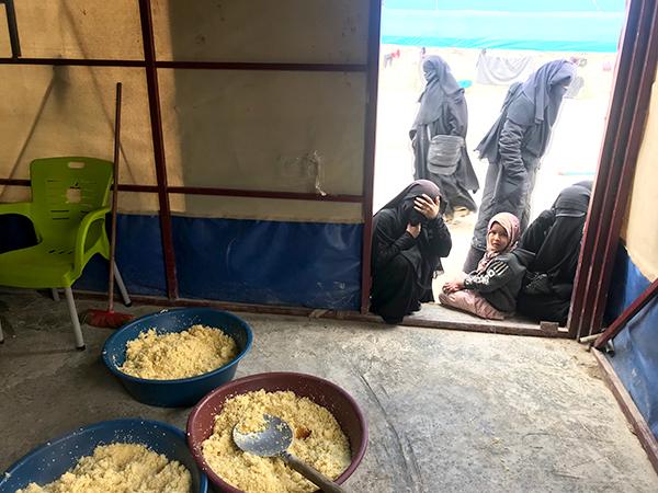 IDP women look into a food prep area at Al-Hol.