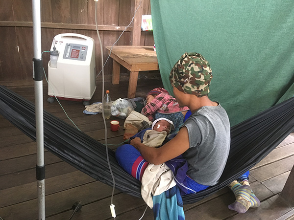 A baby with severe pneumonia uses the oxygen concentrator, now run by solar power instead of fuel.