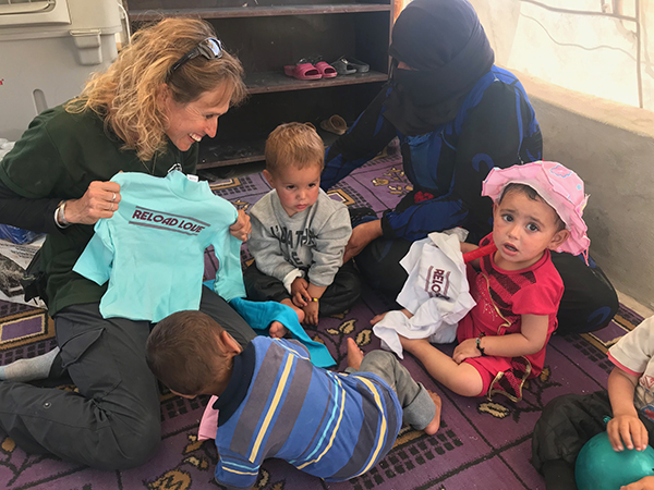 Karen Eubank given shirts from Reload Love to kids in Al-Hawl.