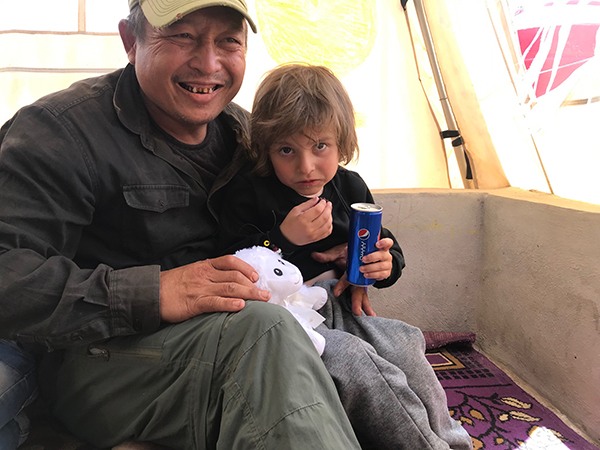 Eliya gives a stuffed lamb from ATP Ministries to a new friend in Al-Hawl.