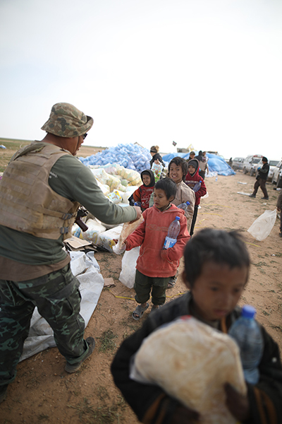 Zau Seng distributing food and water to ISIS children who had just fled Baghouz, Syria.