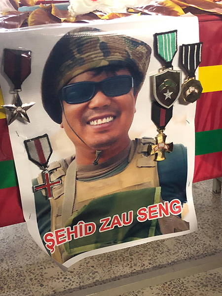 Zau's photo and medals on pinned to his coffin.