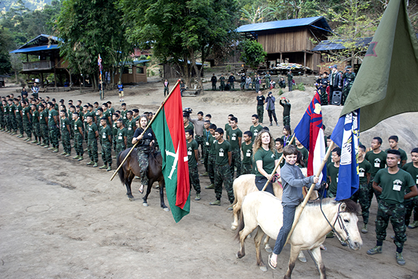 Peter, Suu, and Sahale Eubank open the graduation ceremonies by carrying in FBR, Louisiana, Karen, and Kachin flags