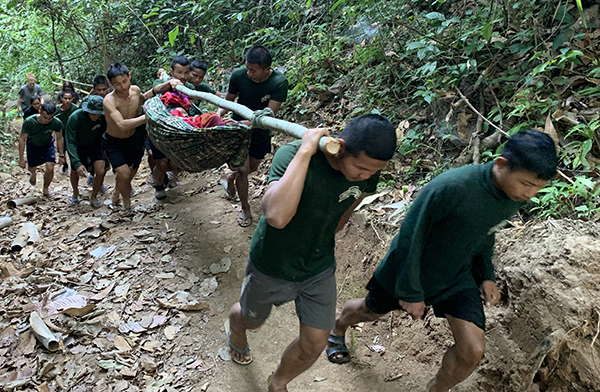 A patient is carried to the Jungle School of Medicine-Kawthoolei (JSMK) via bambulance - a carrying device made of a hammock and bamboo
