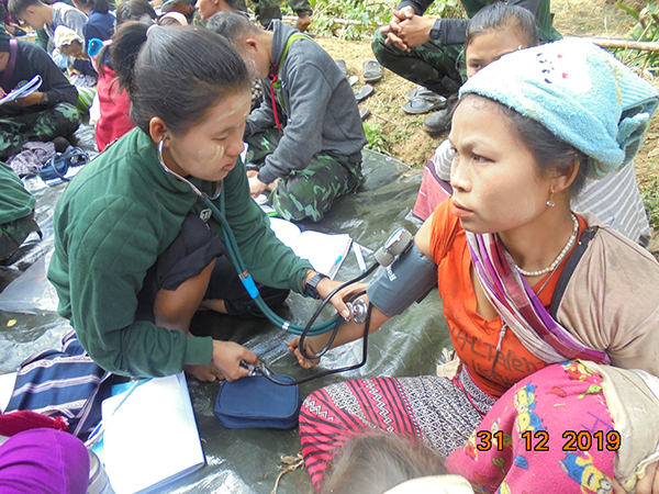 A medic checks the blood pressure of a local villager