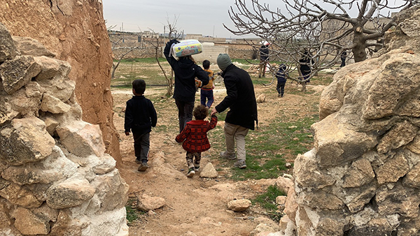 Families bring the food back to abandoned homes they are staying in outside Manbij
