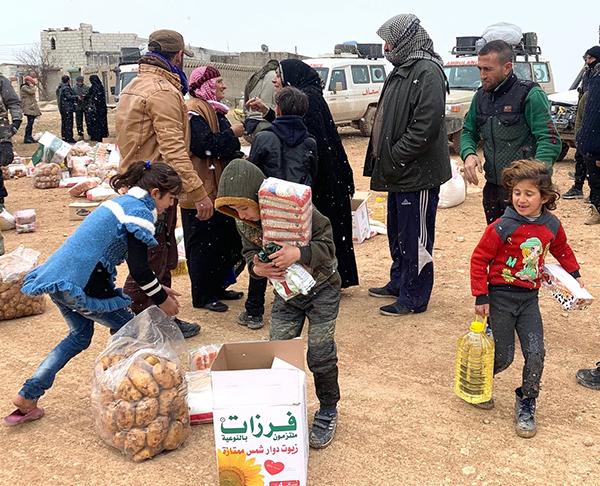 Families who fled Idlib receive food outside Manbij, Syria