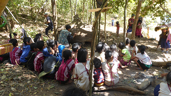 School continues in the jungle by using a fallen tree as a chalkboard