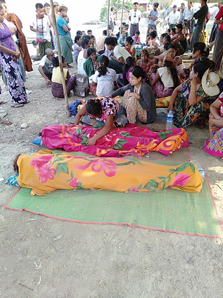 Villagers wrap up the bodies of the deceased