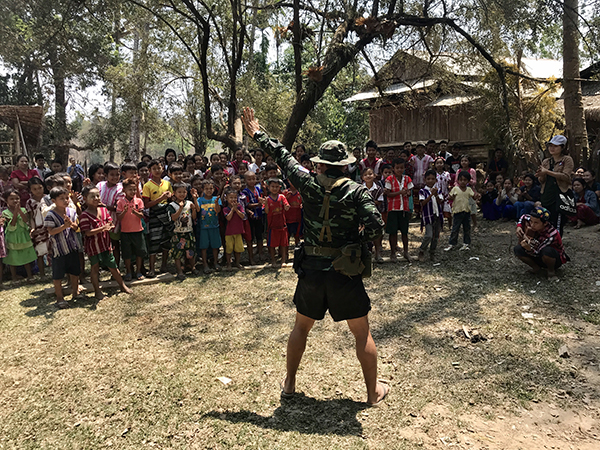A Ranger teaches a song to villagers during a GLC program.