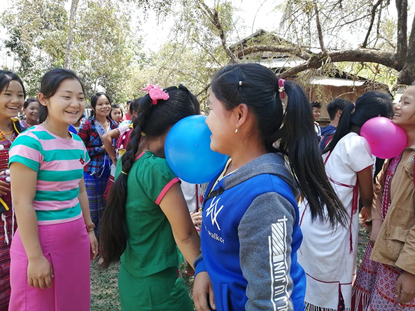 During a Good Life Club program, villagers play a game where they must pop a balloon between their neck and shoulders.