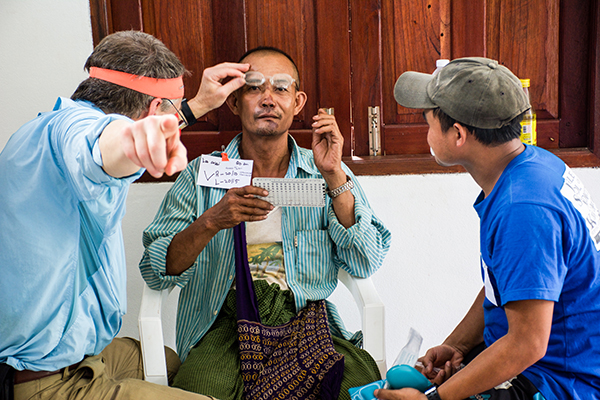 Hser Eh Too and Dr. Bob Arnold fit a Karen patient with reading glasses.