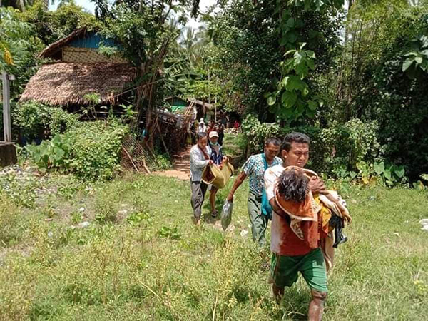 Villagers carry the victims of the attack