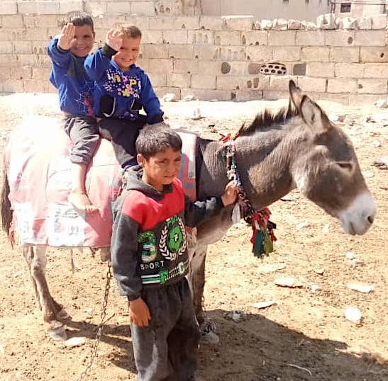 Hatam, brothers and donkey that was killed when he was hit by Turk mortars