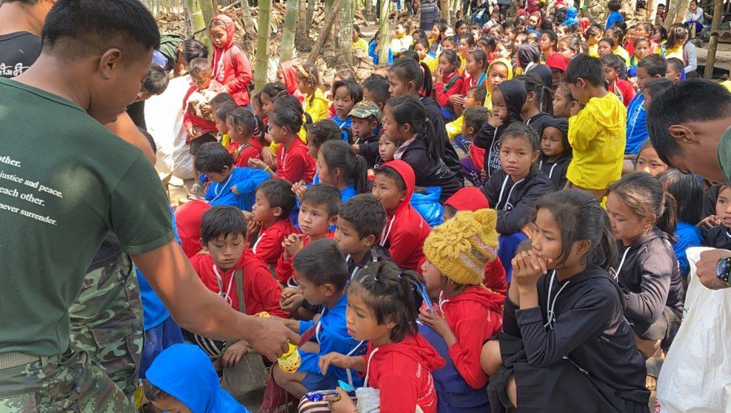 Arakan, Karenni and Karen team members give out snacks to the kids