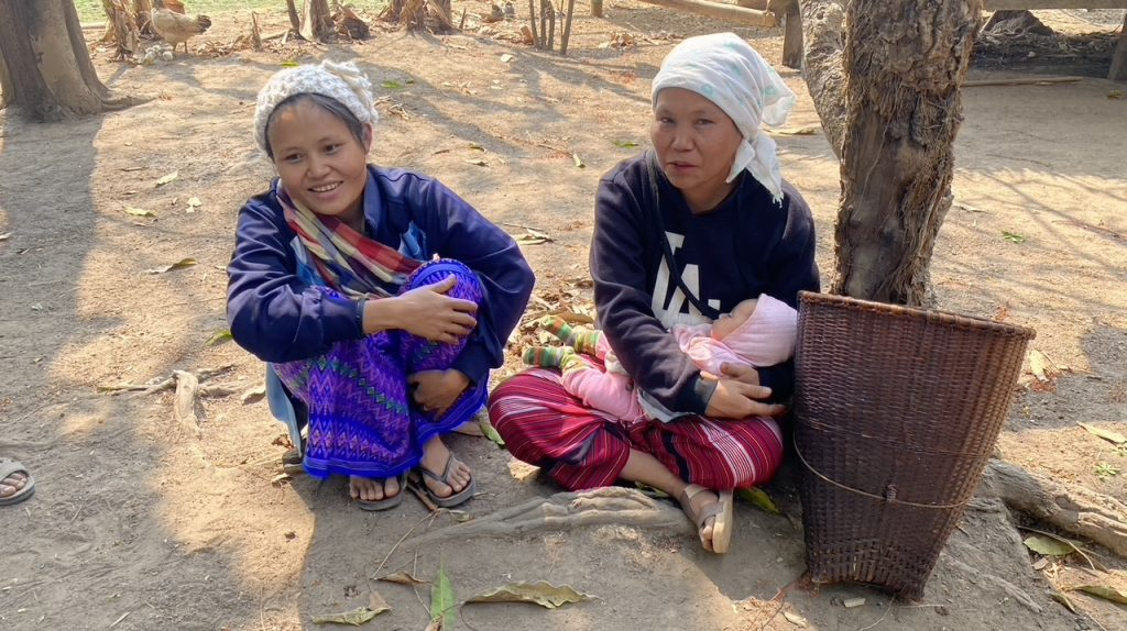Displaced mothers watch their children have fun
